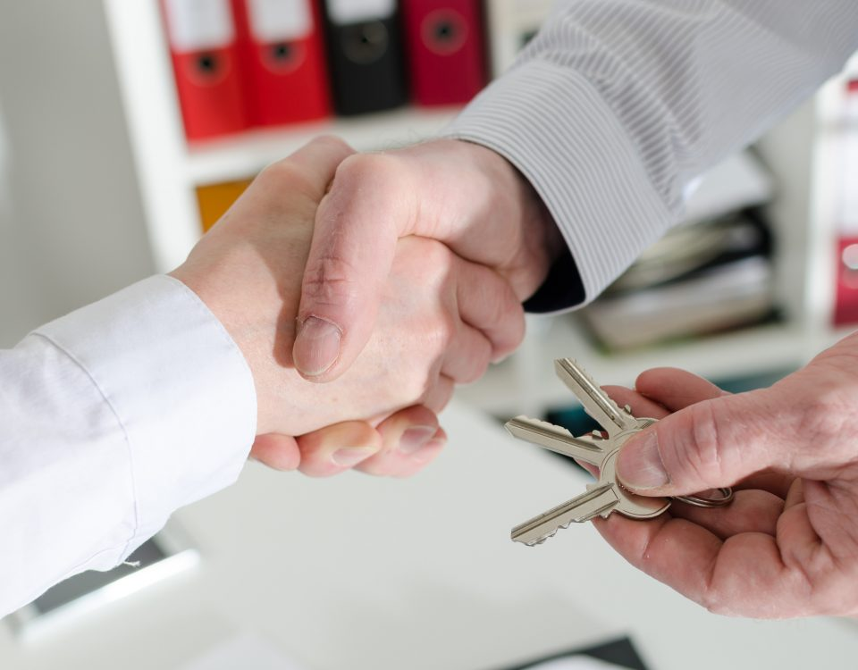 Realtor shaking hands with his client by delivering the keys, closeup